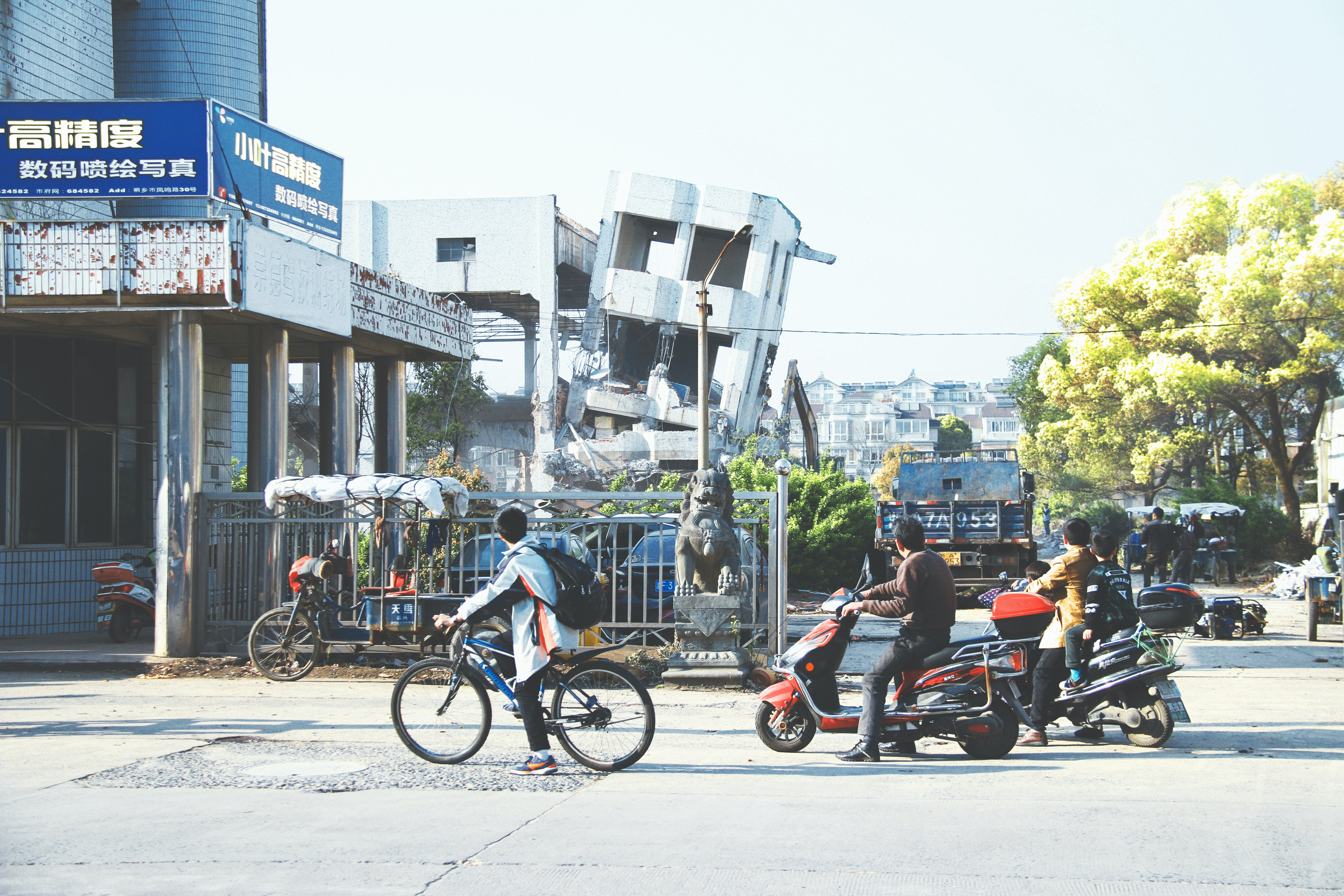 three men riding bicycle and motor scooters near building at daytime