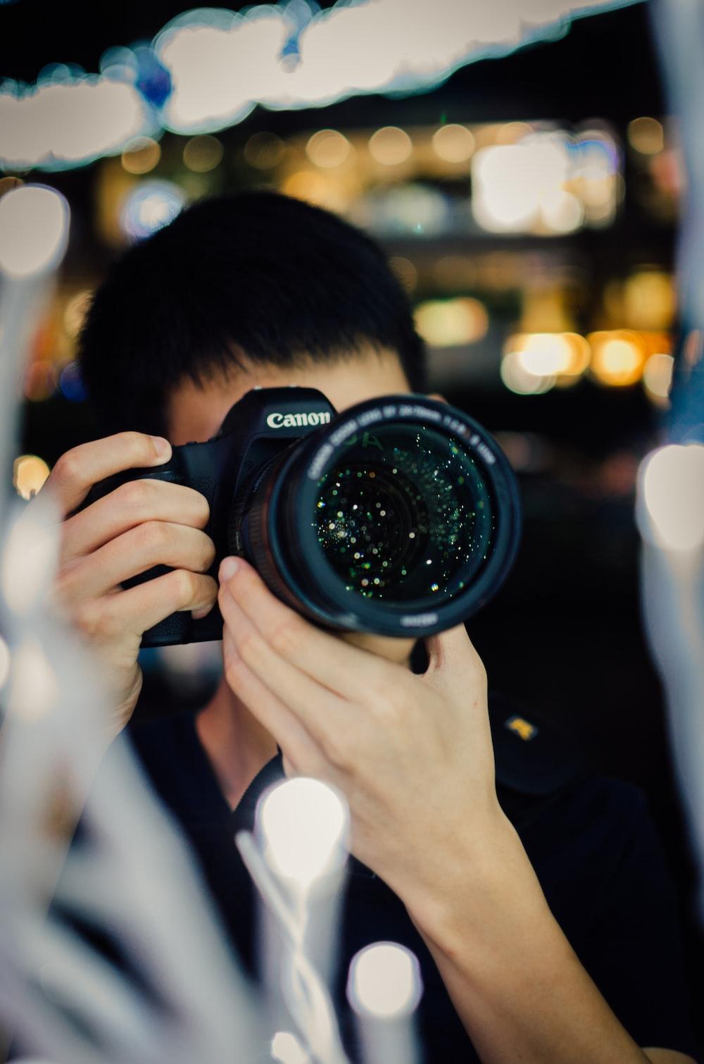 person using black Canon DSLR camera