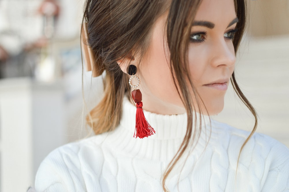 focus photography of woman wearing red tassel earrings while looking on her left side
