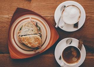 ham sandwich on plate near cappuccino on mug and coffee