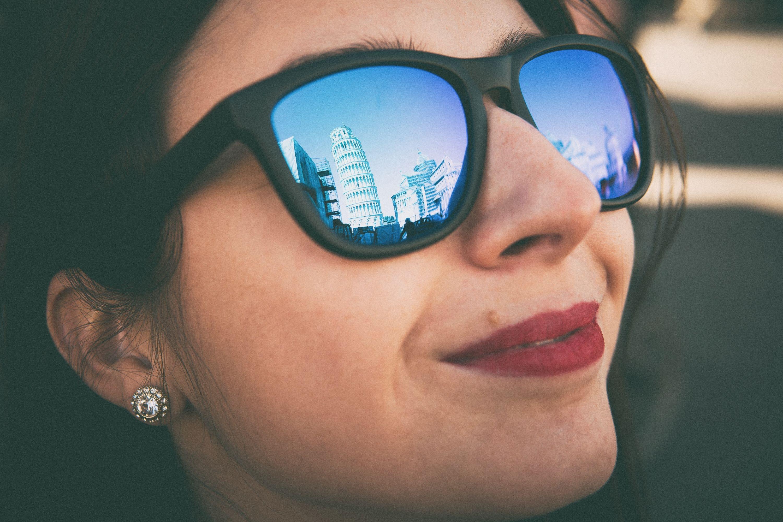 closeup photography of woman wearing black Wayfarer-styled blue lens sunglasses