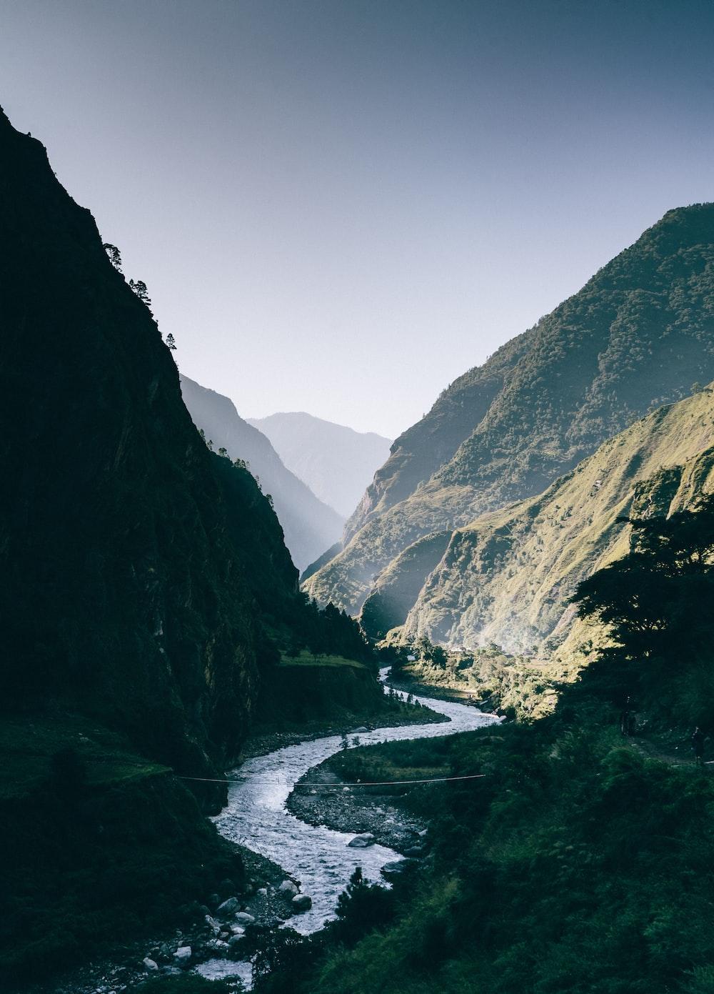 river between mountain at daytime