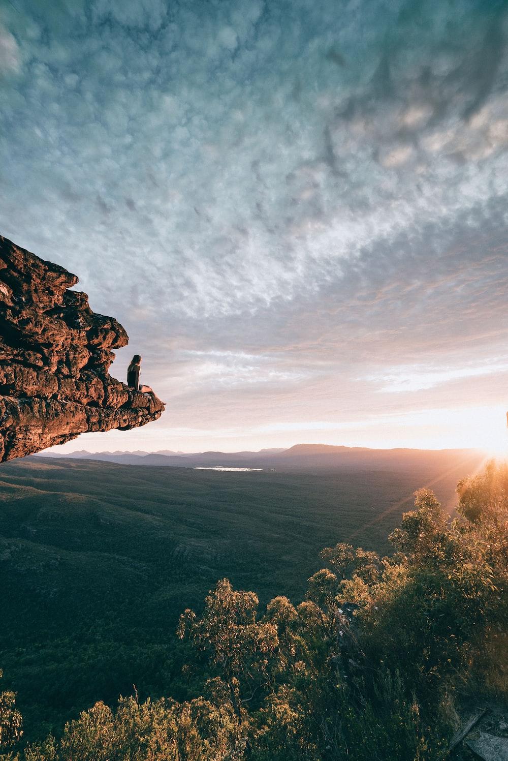 man sitting on mountain rock