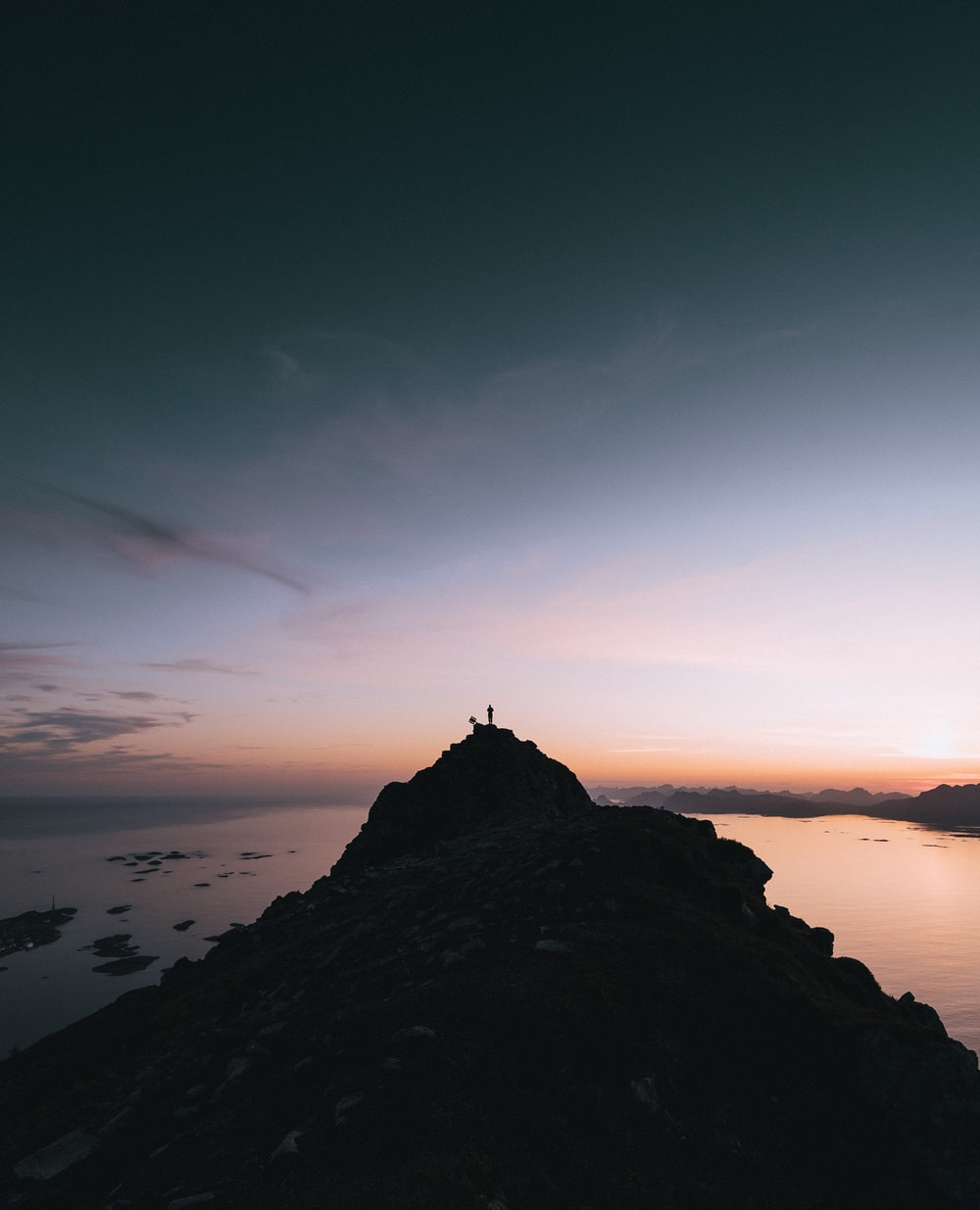 silhouette on person standing on top mountain cliff