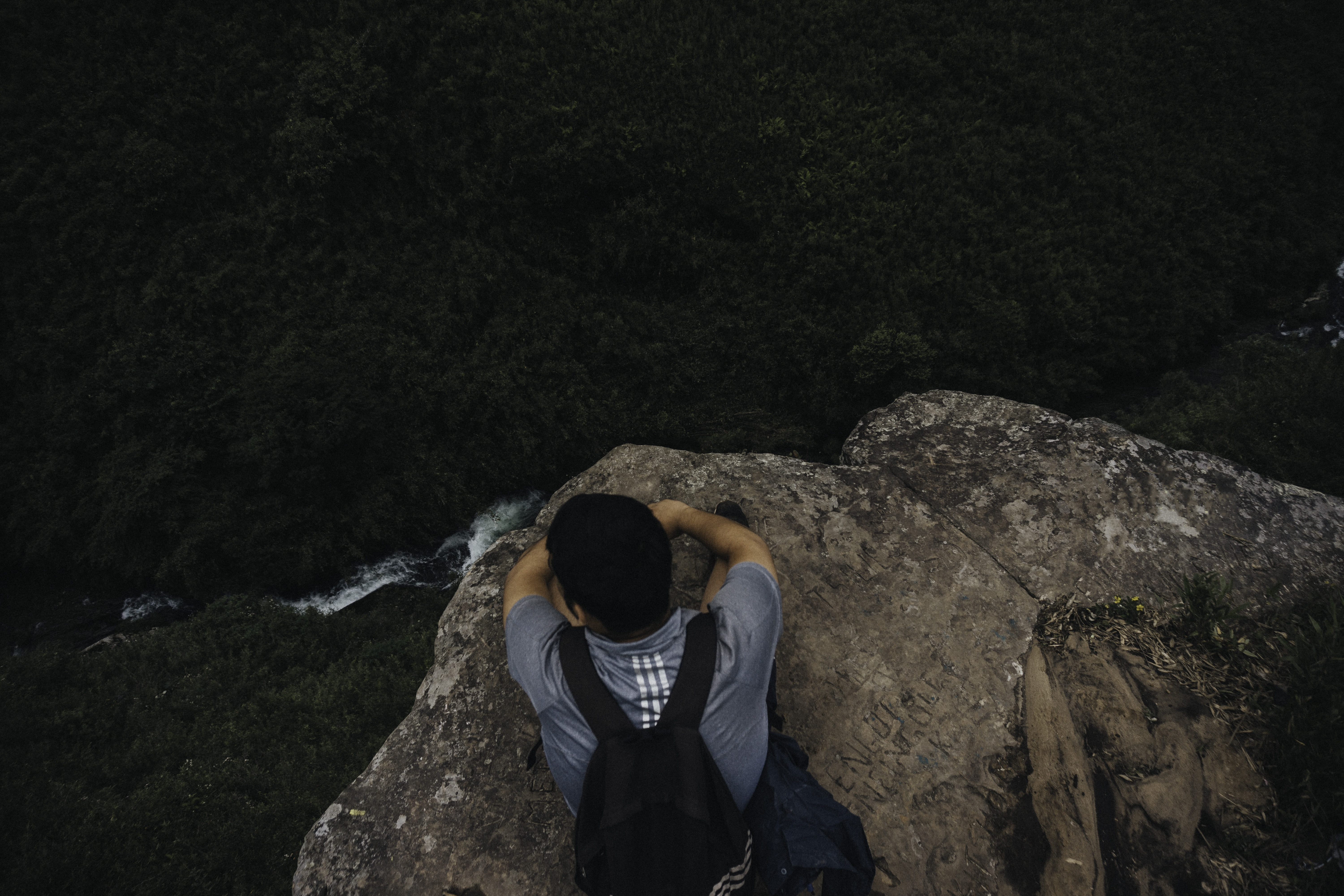 man sitting on the edge of cliff
