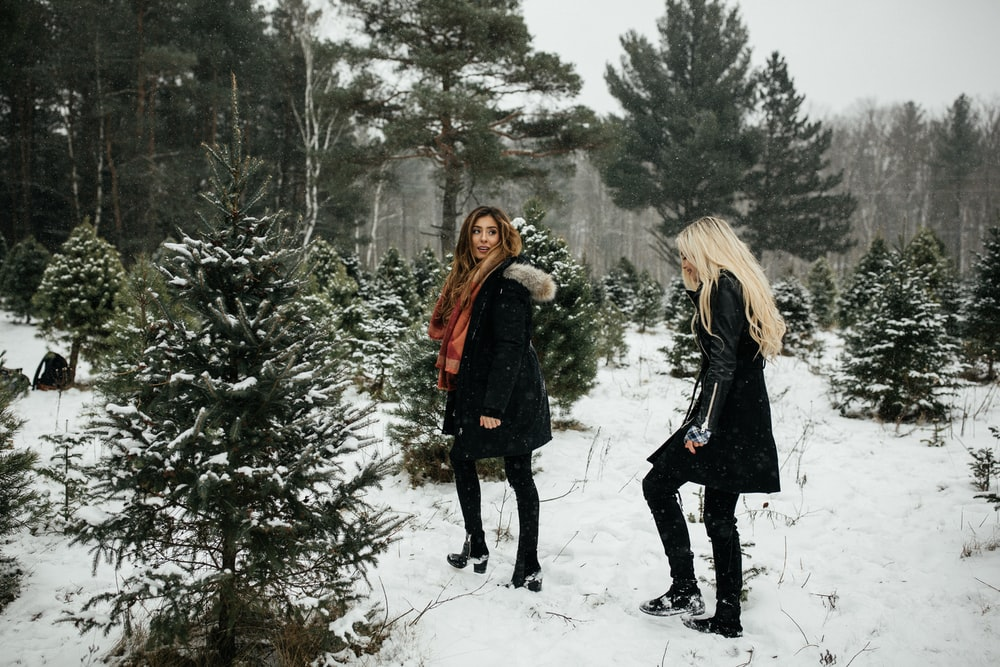 two woman walking towards snow