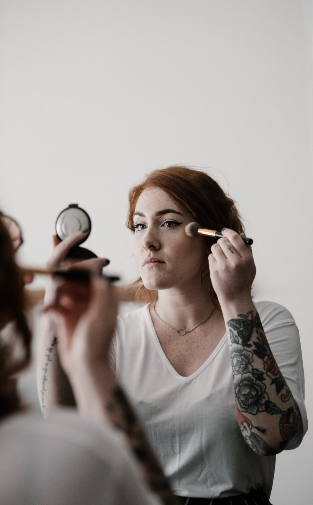woman putting makeup on her face