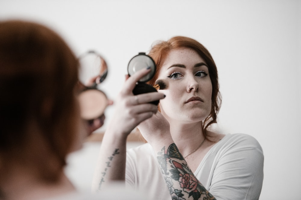 selective focus photography of woman applying blush-on on her face