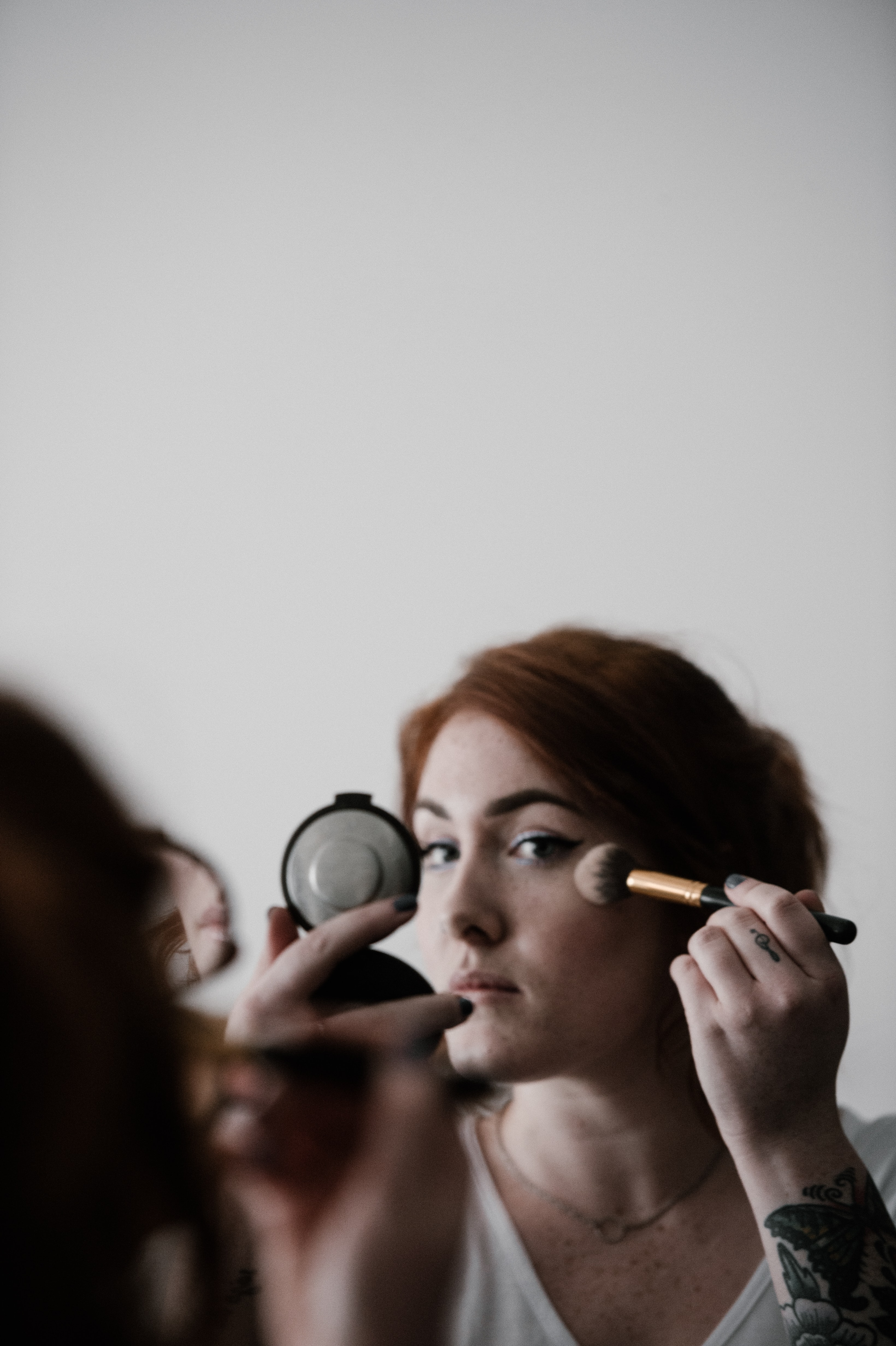 woman doing makeup infront of mirror