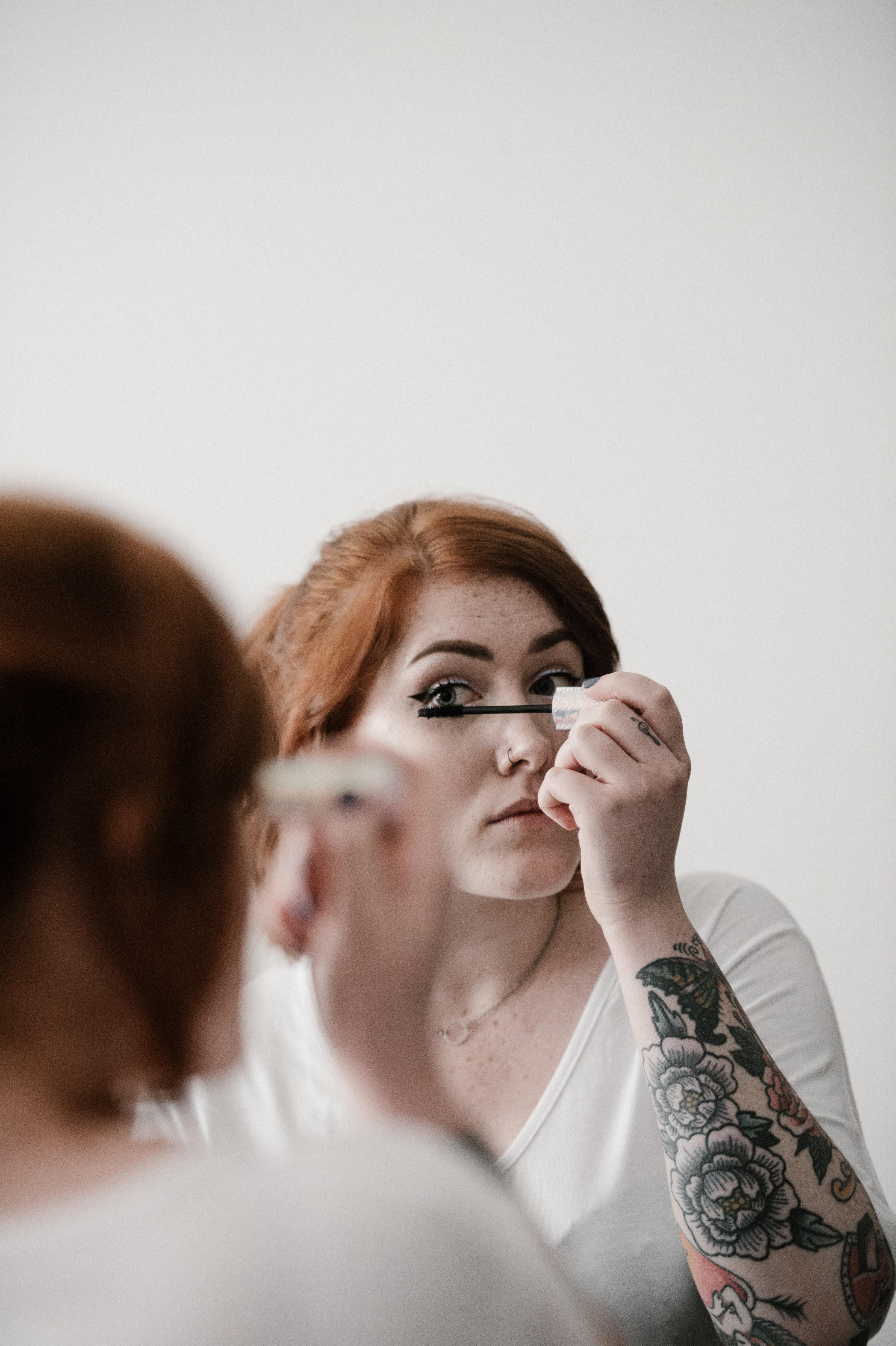 woman using makeup during daytime