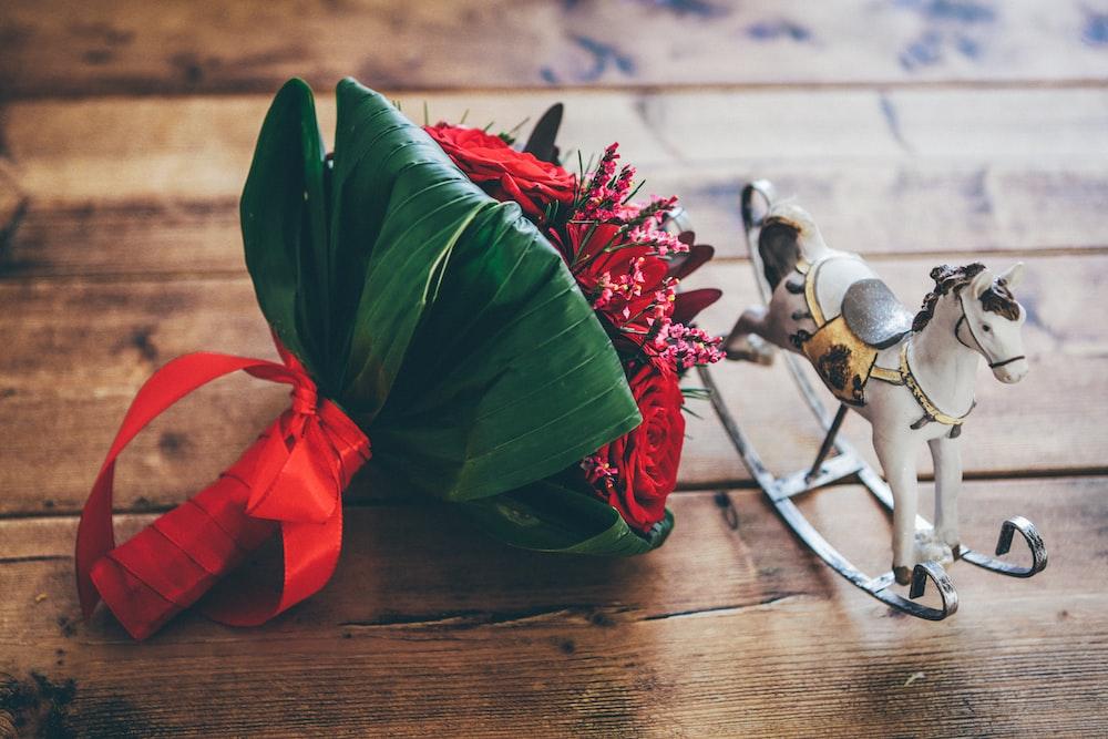 rocking horse beside flower bouquet