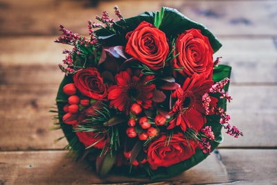 red flower bouquet on brown surface bouquet teams background