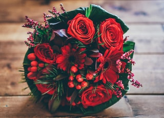 red flower bouquet on brown surface