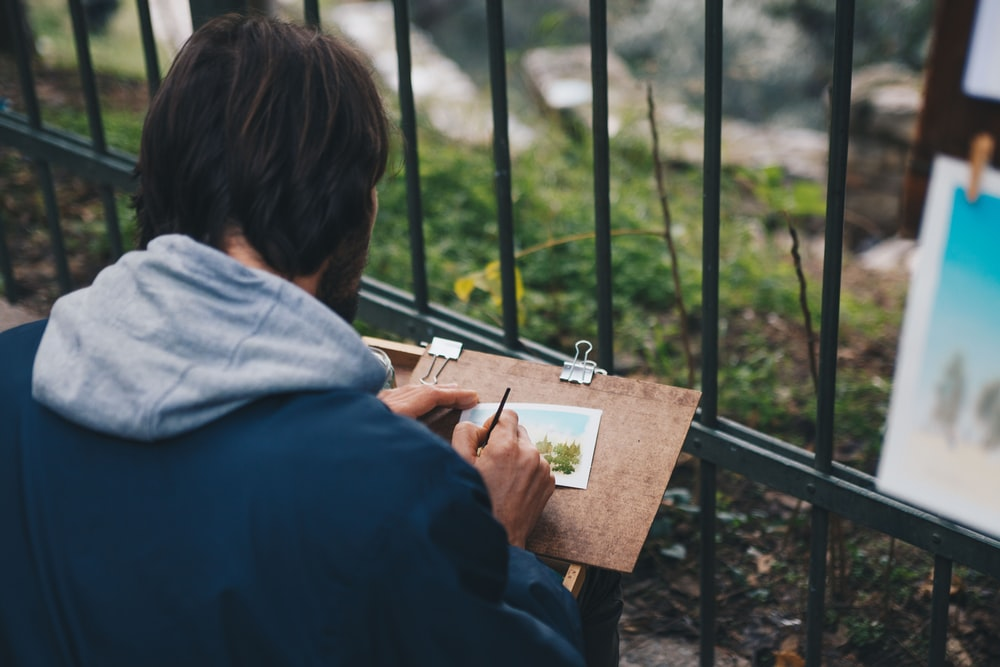 man drawing on paper beside fence