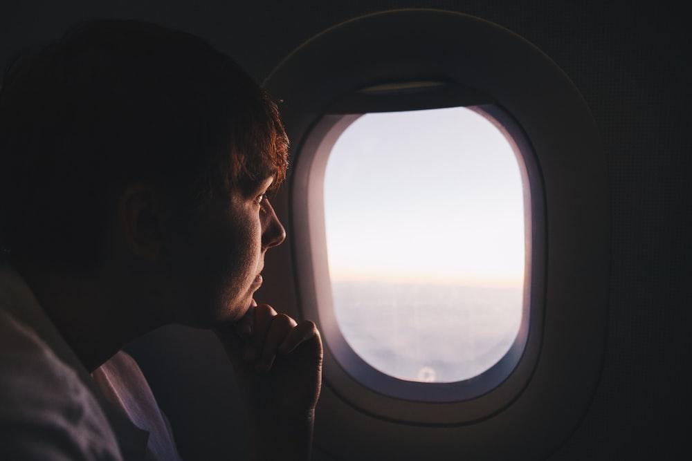 man looking at window inside plane