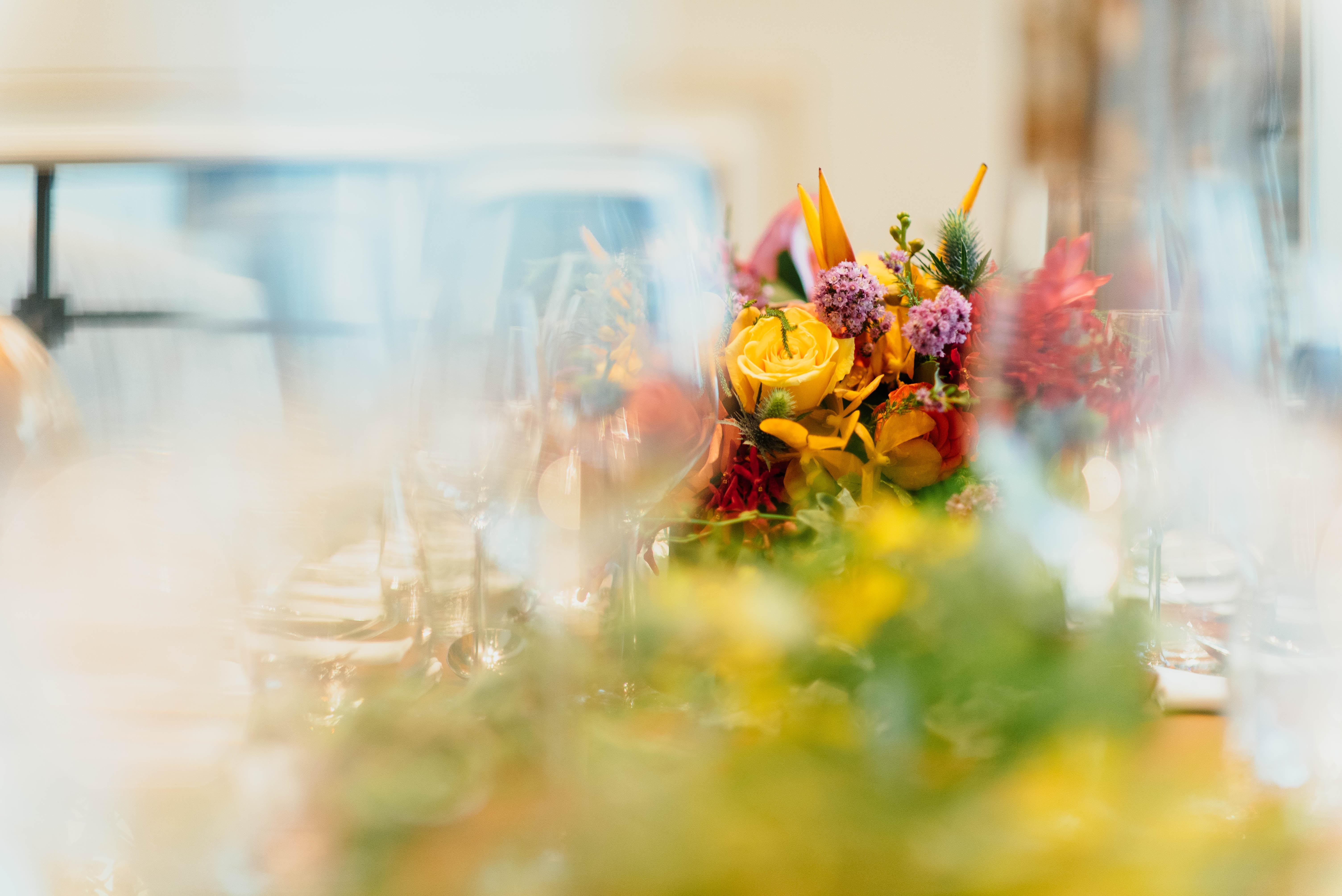 tilt shift lens photography of yellow flower near wine glass