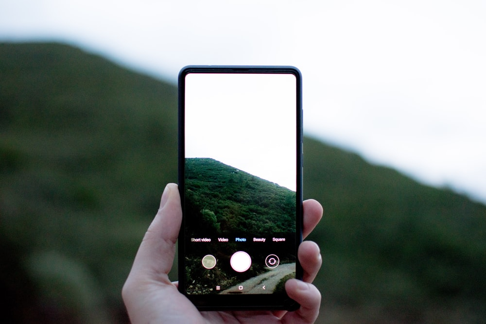person showing photo of mountain on smartphone