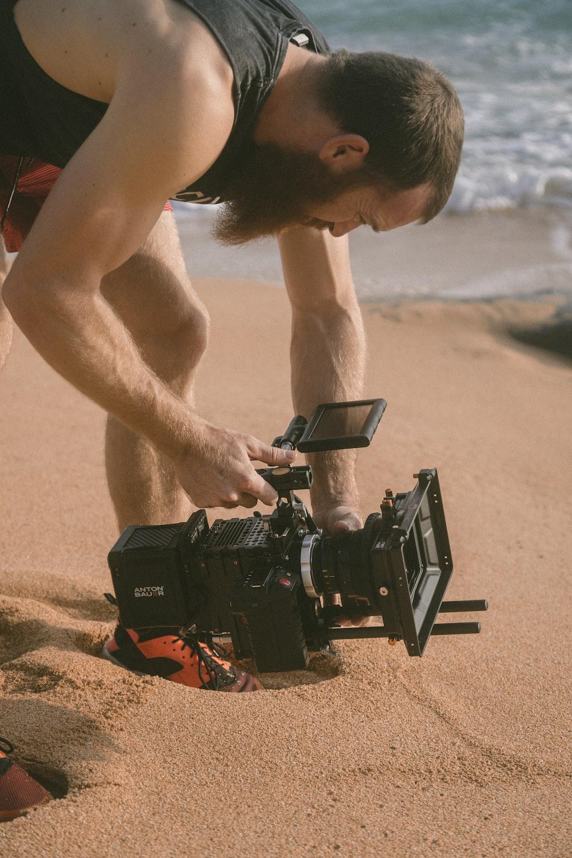 man holding film recorder near seashore