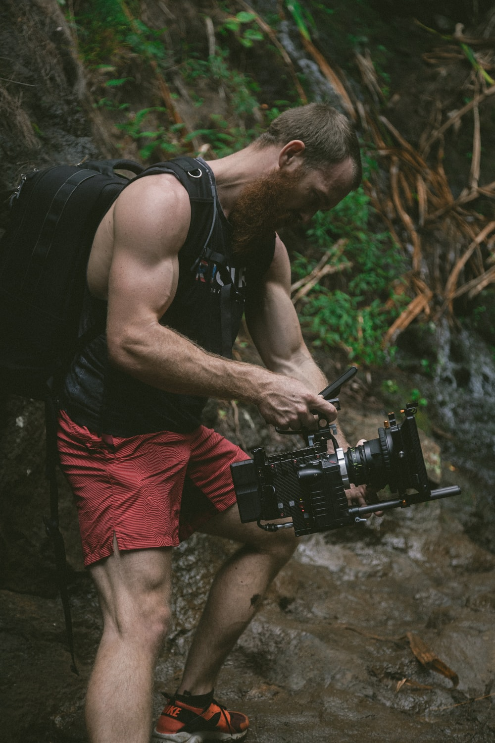 man holding black camera and backpack