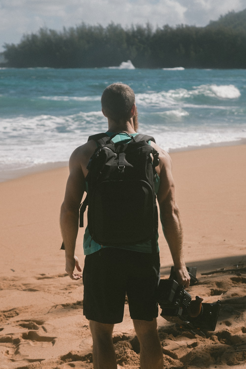 man carrying video camera standing on beach sand facing sea