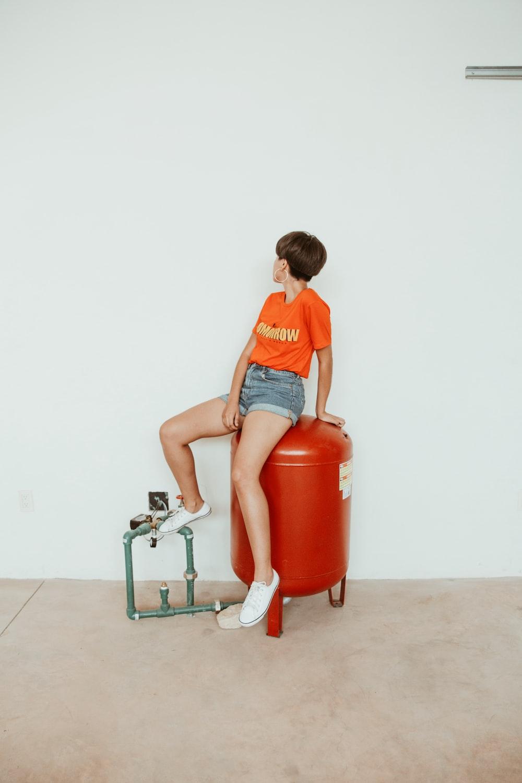 woman sitting on red metal tank