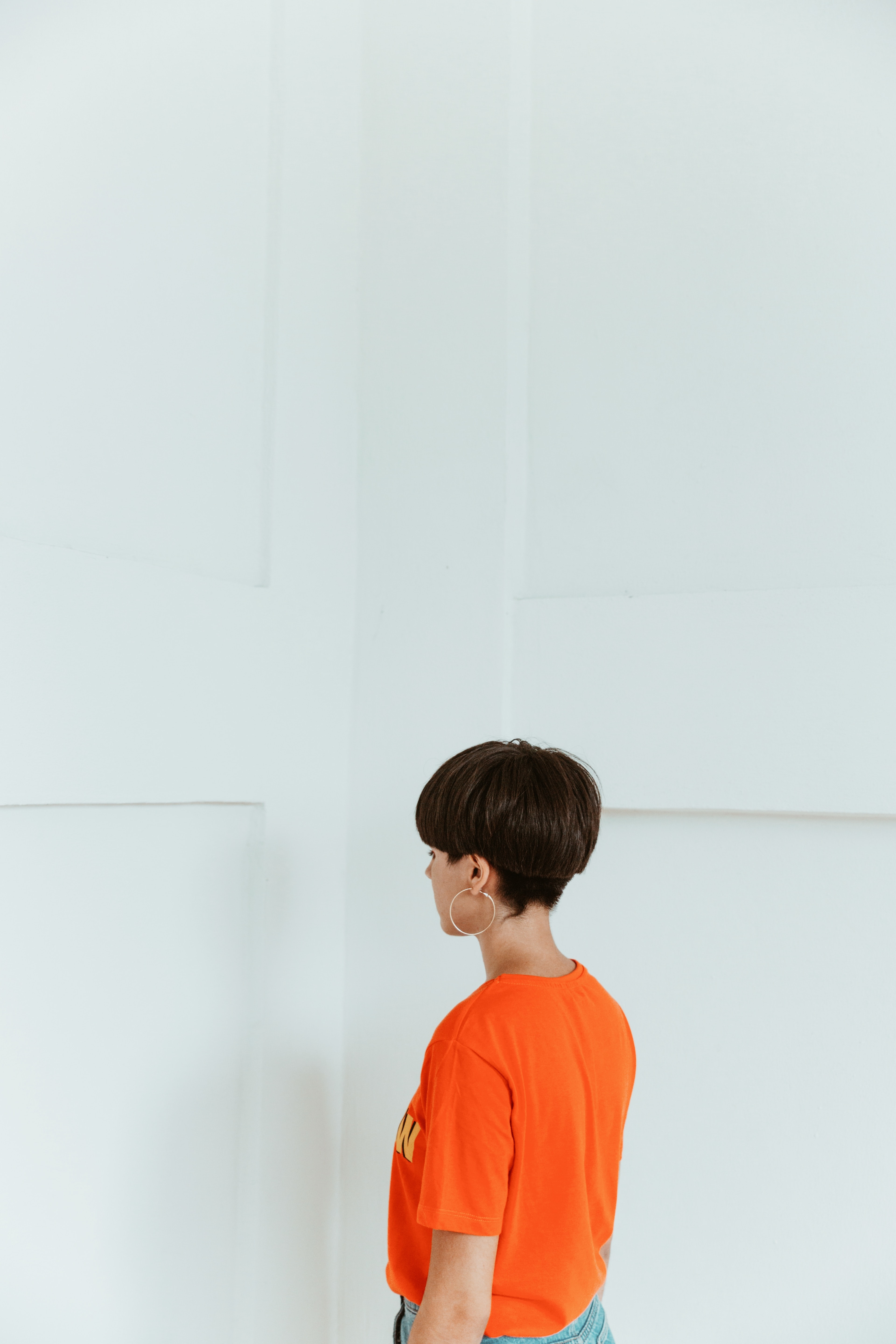 woman wearing orange shirt facing white wall