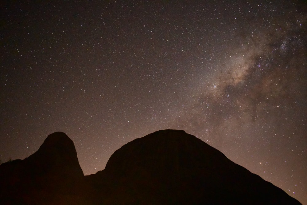 silhouette of mountain with starry night