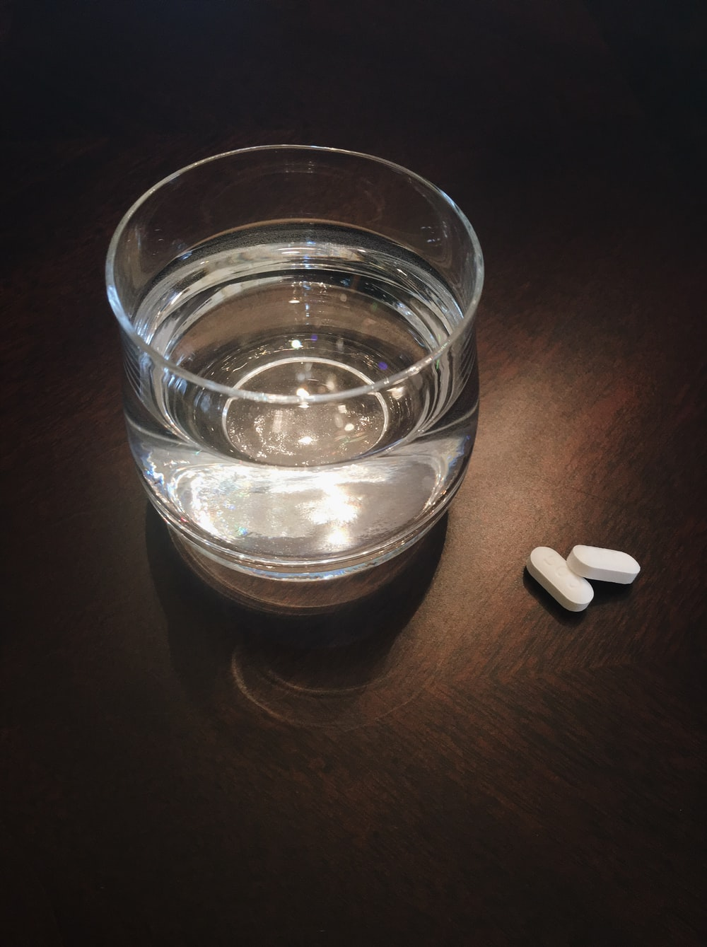 two oval white medication tablets on brown surface