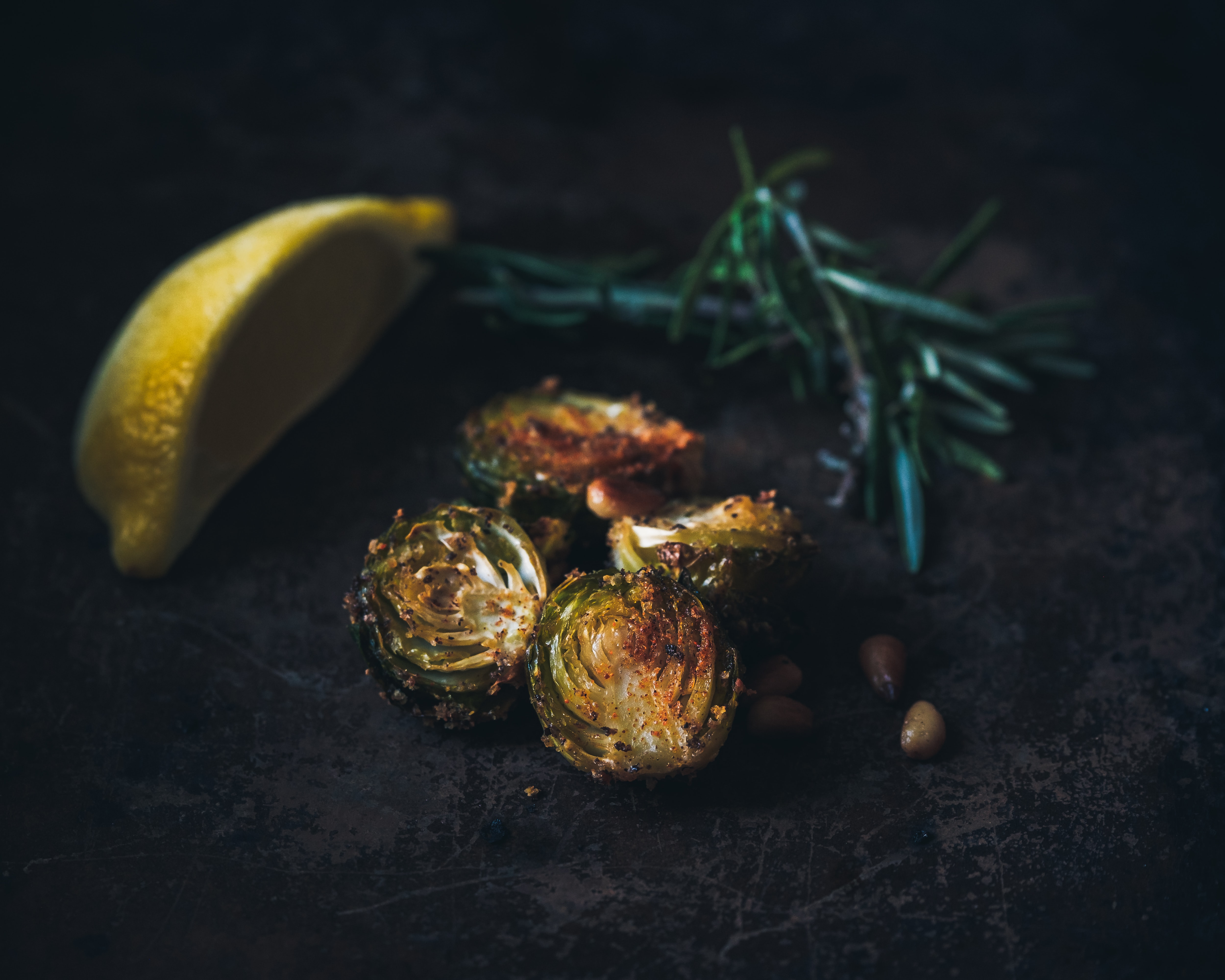 selective focus photography of grilled Brussels sprout, lemon wedge, and rosemary sprig