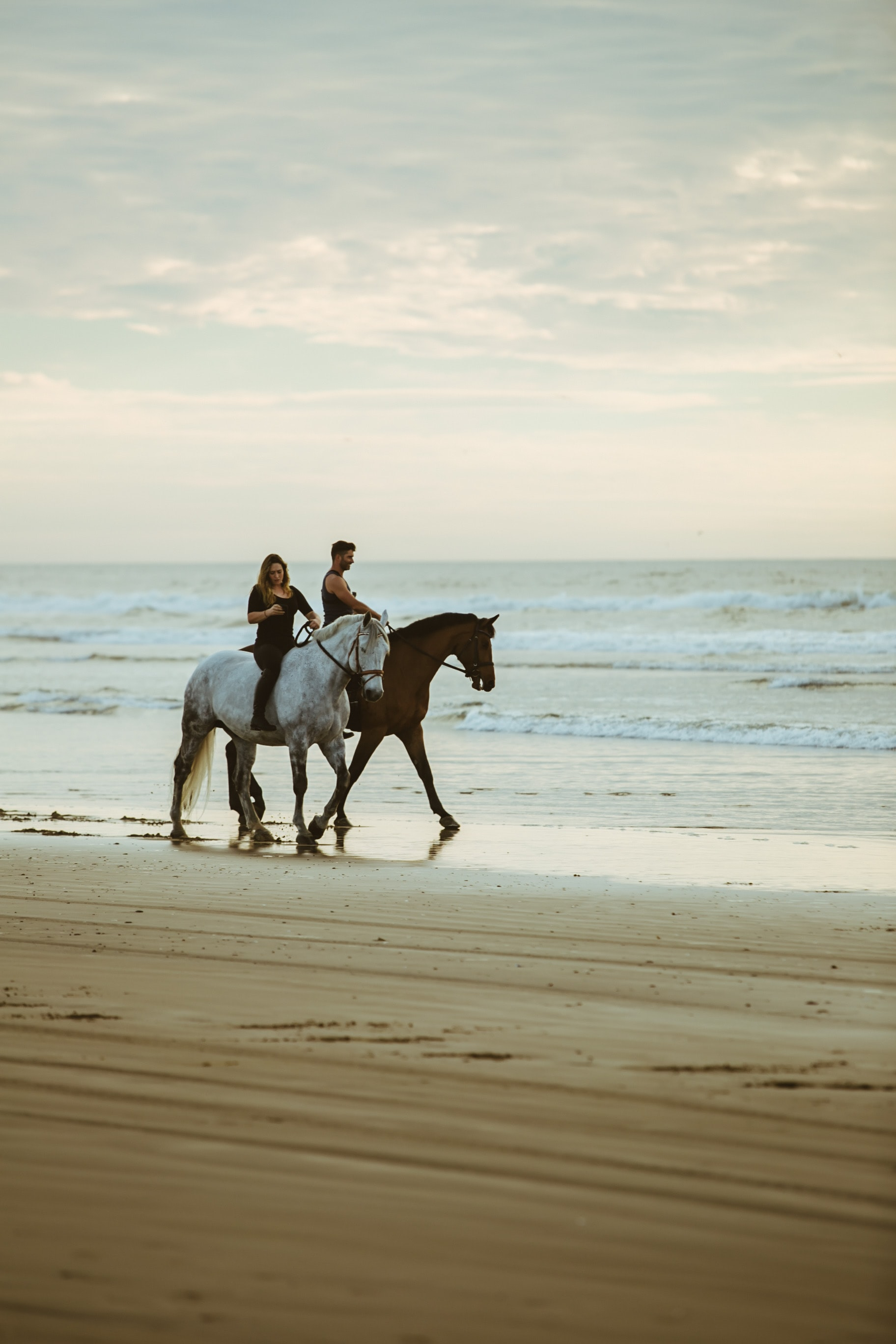 man and woman riding on horse near seashore