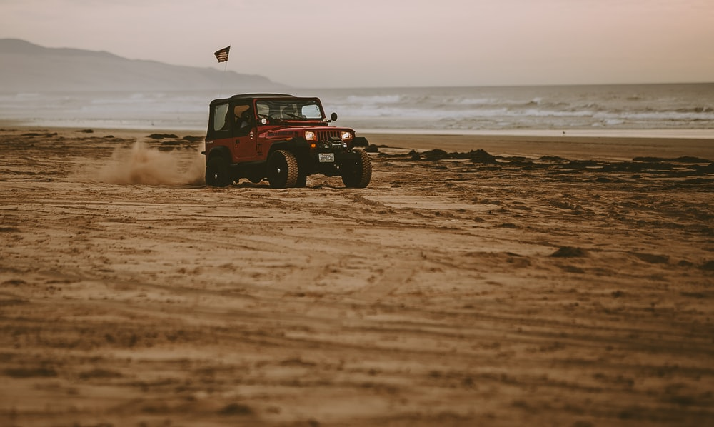 red Jeep Wrangler on seashore near body of water at daytime