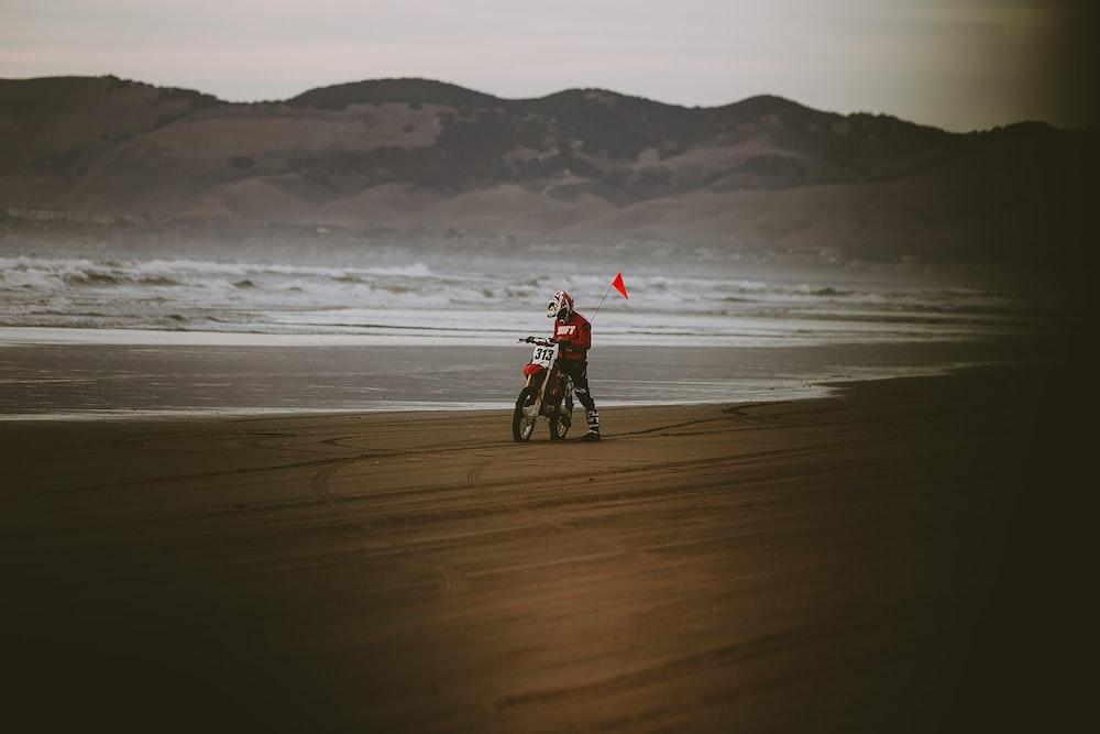 man riding motocross dirt bike near seashore