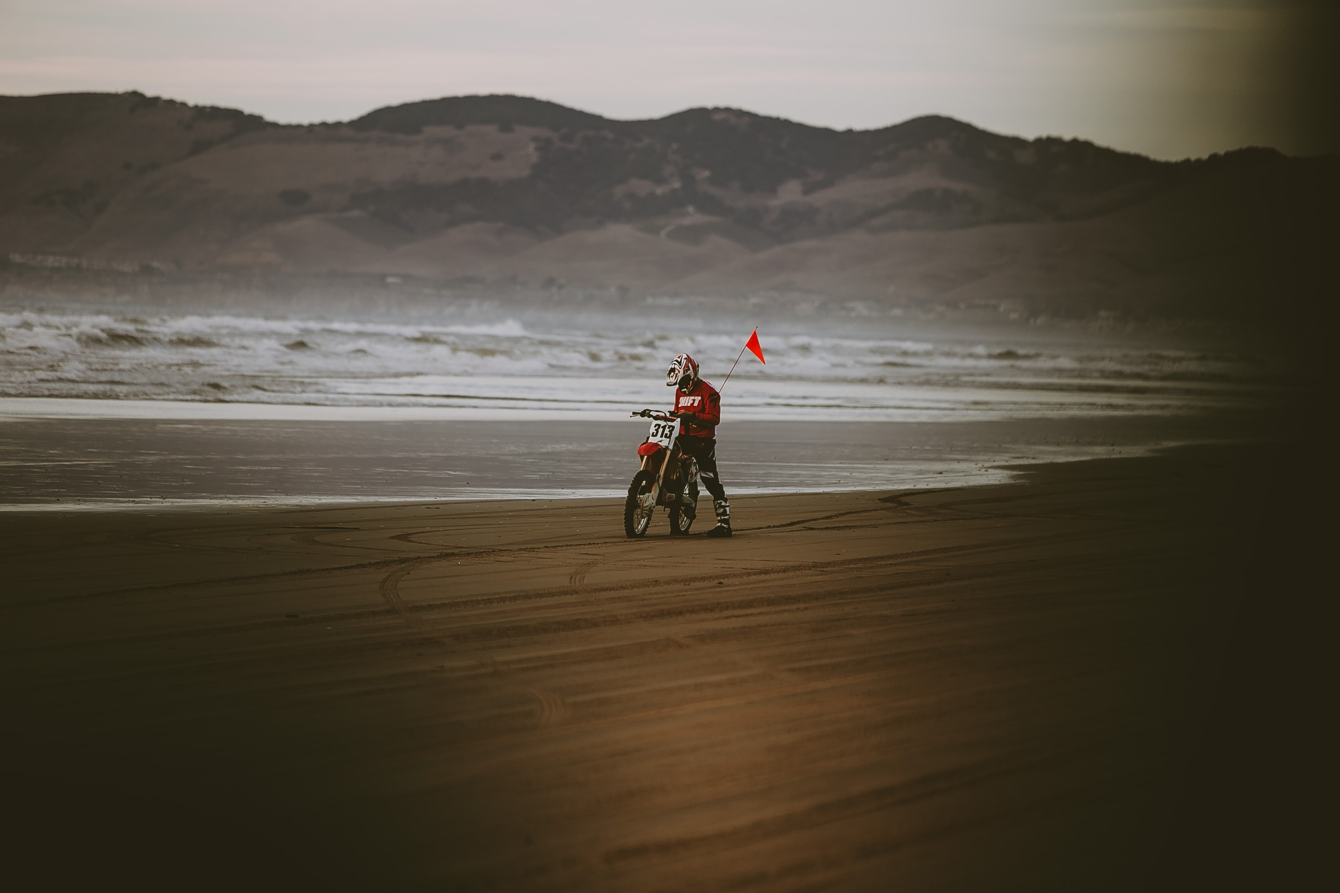 man riding motocross dirt bike near seashore
