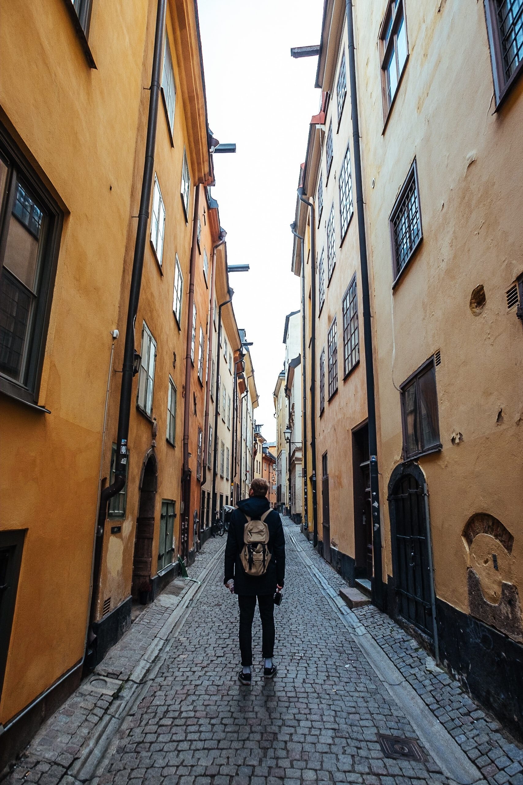 man in black long-sleeved top and brown backpack walking on street