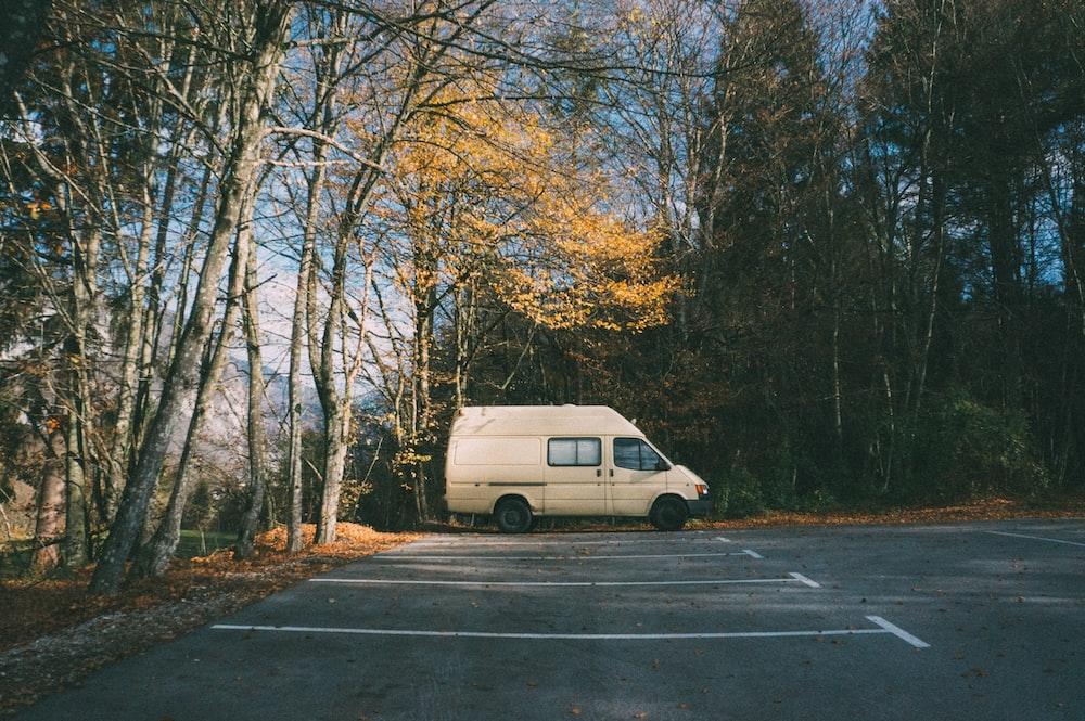 white minivan parked near trees at daytime