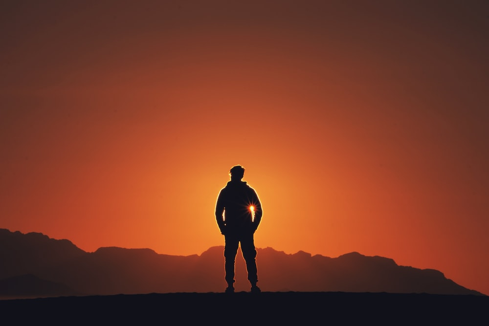 silhouette photography of person standing on platform with mountain background during golden hour