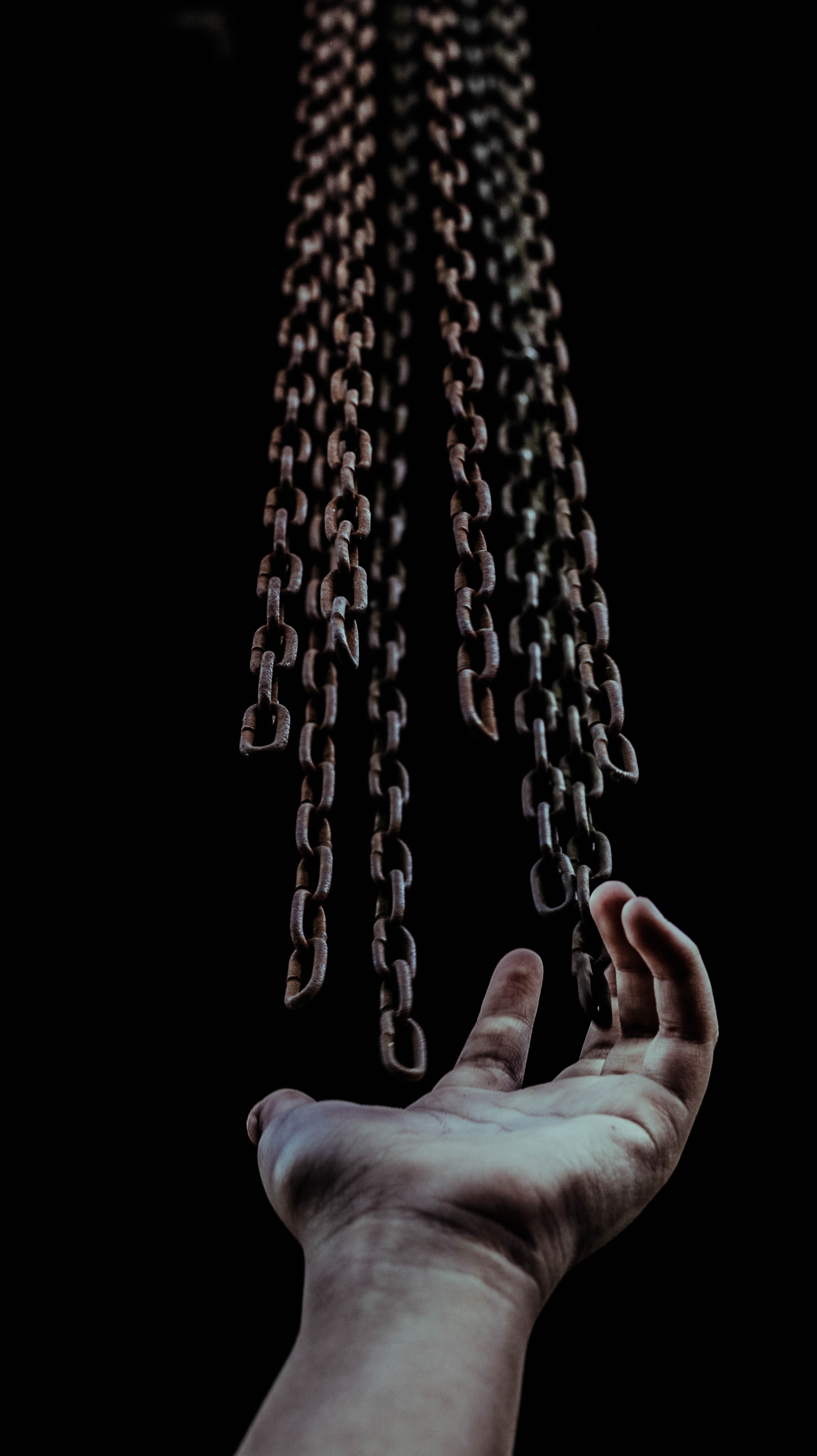 Image of a hand open beneath hanging chains.
