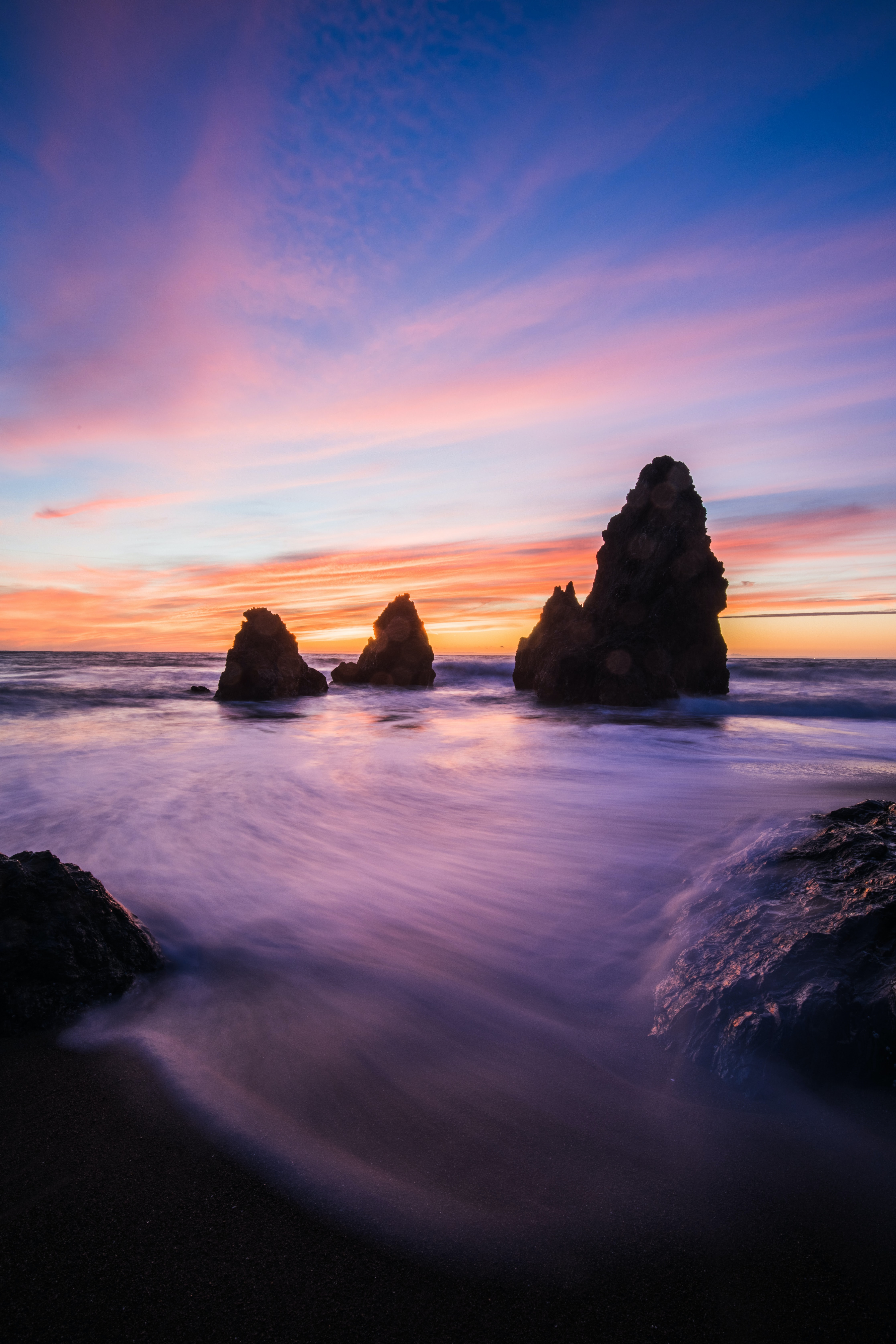 rock formations in body of water at blue hour