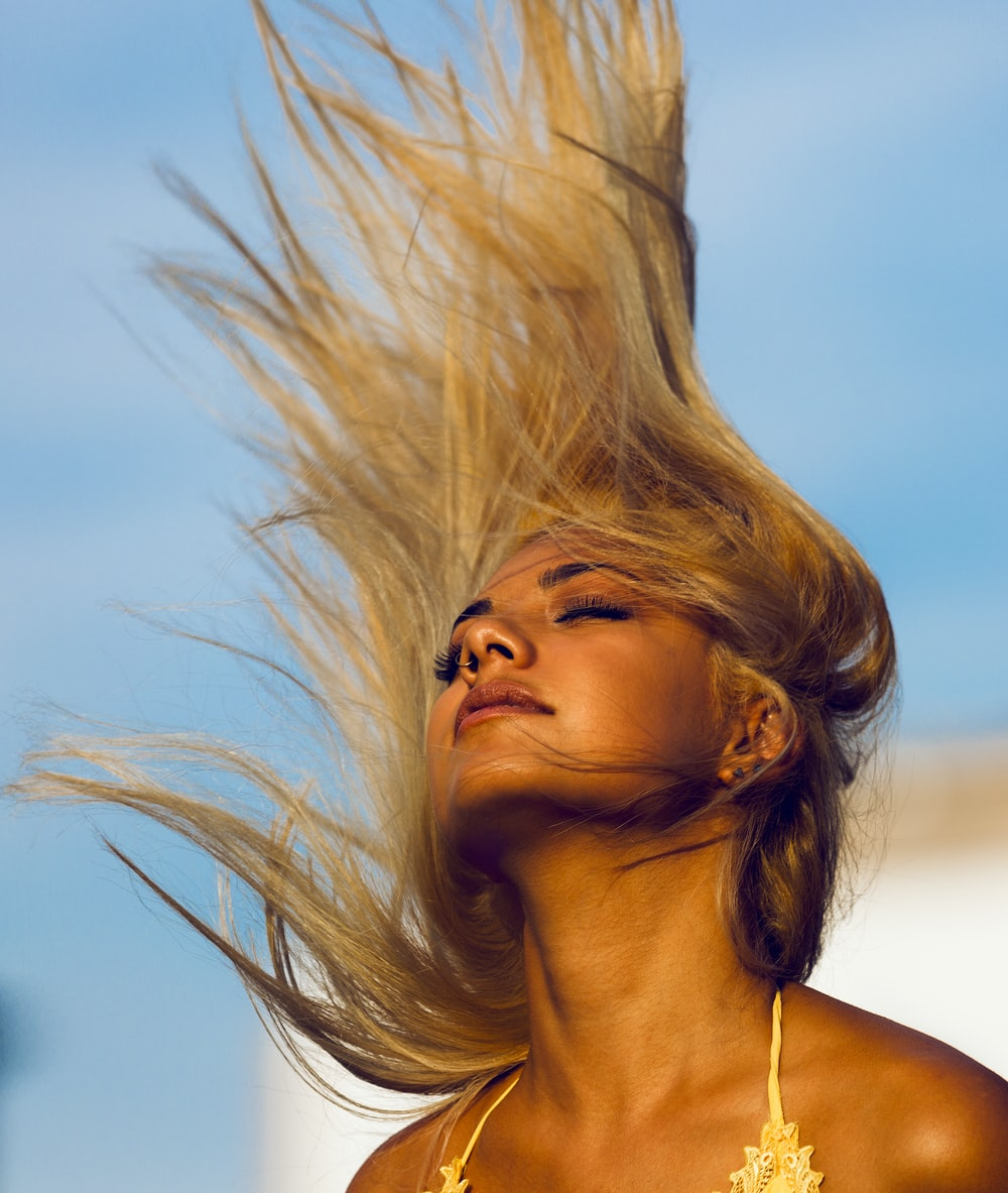 woman wearing yellow halter top whipping hair