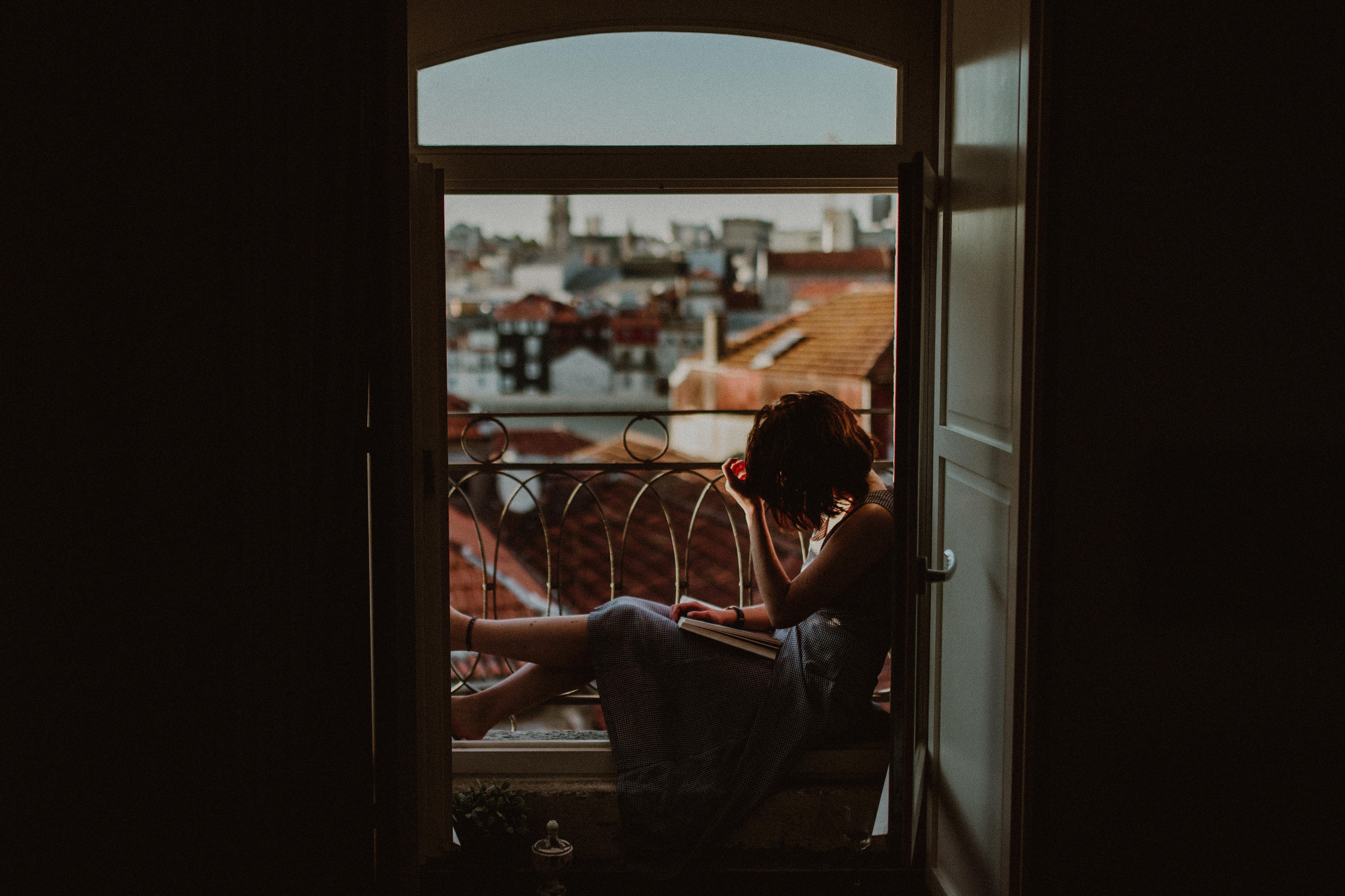 woman wearing gray dress sitting near window during daytime