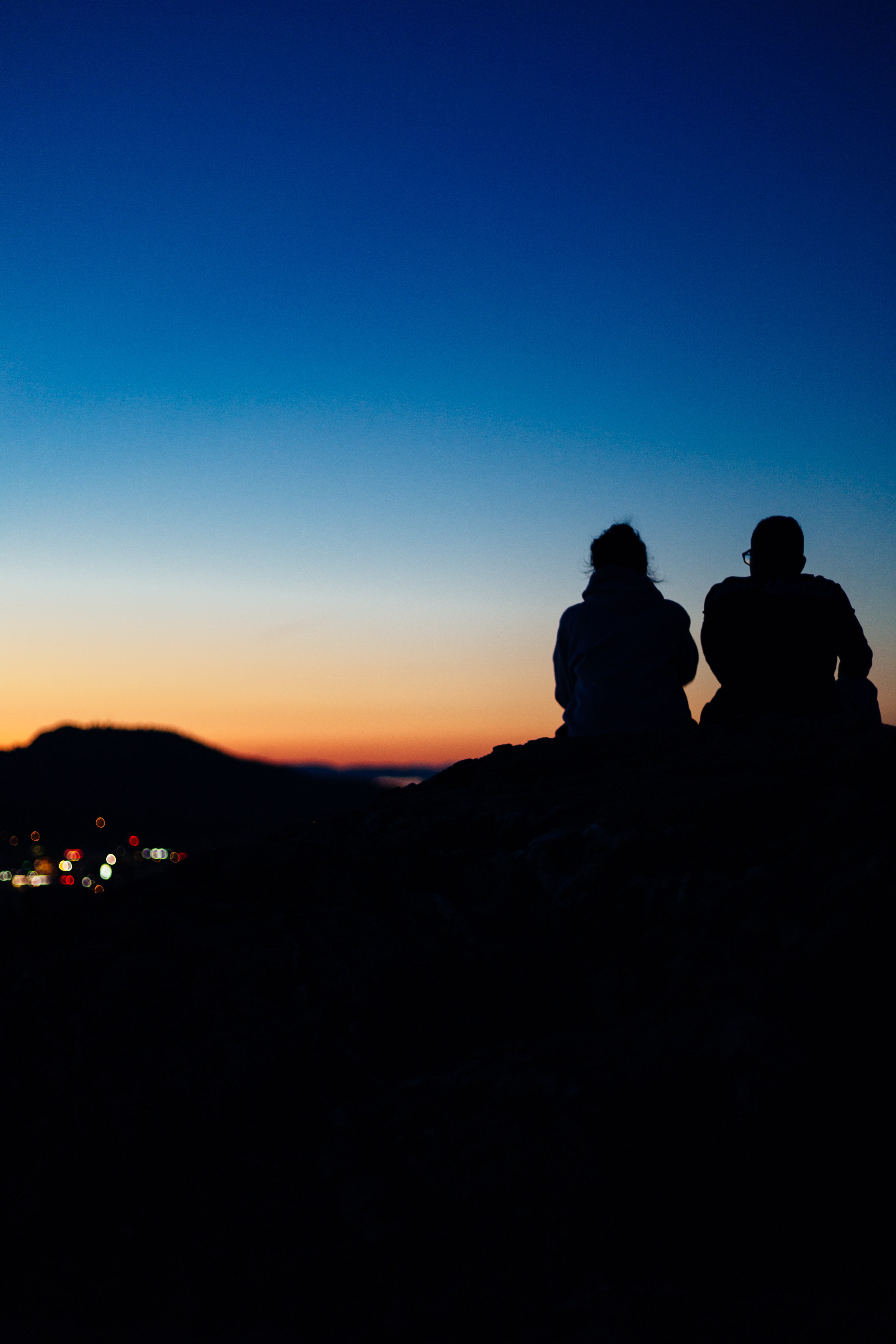 two silhouette people sitting during sunset
