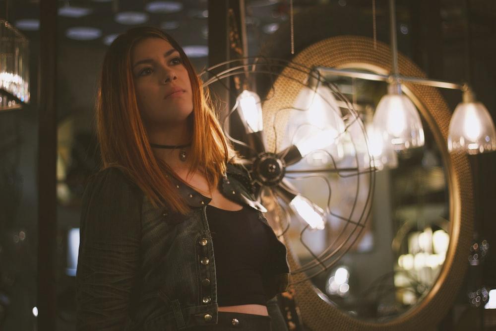 woman standing near pendant lamp