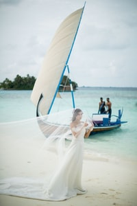 woman wearing white wedding gown with veil walking on shore