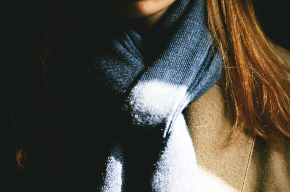 woman wearing brown top and black scarf
