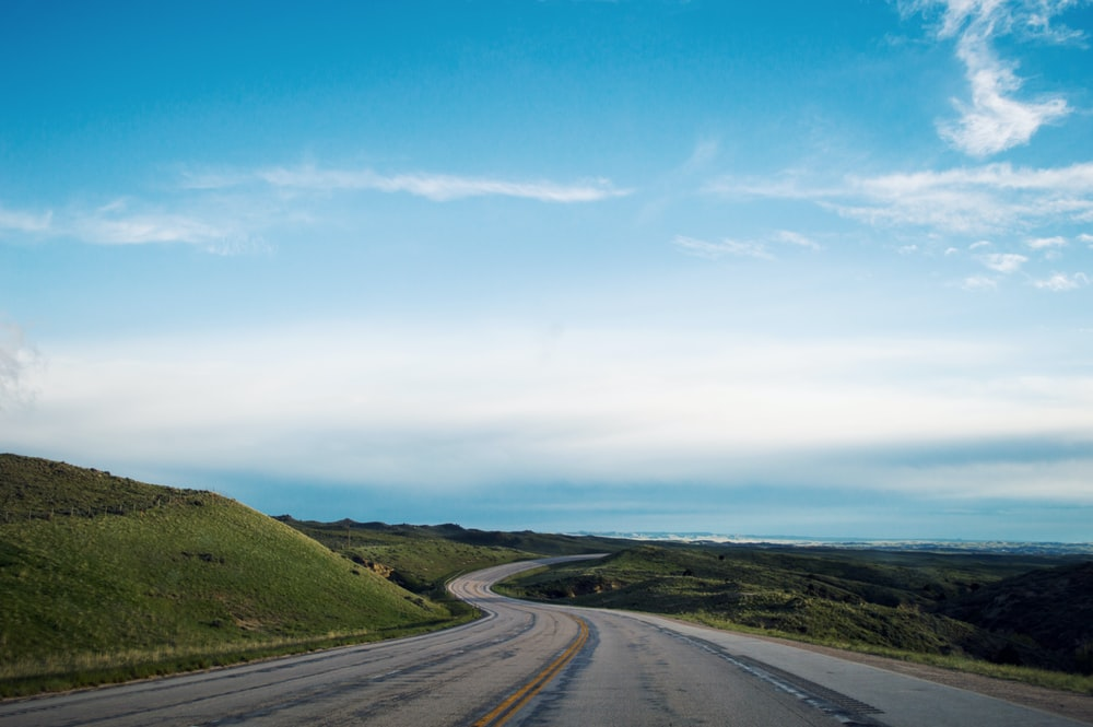 empty gray road under blue sky