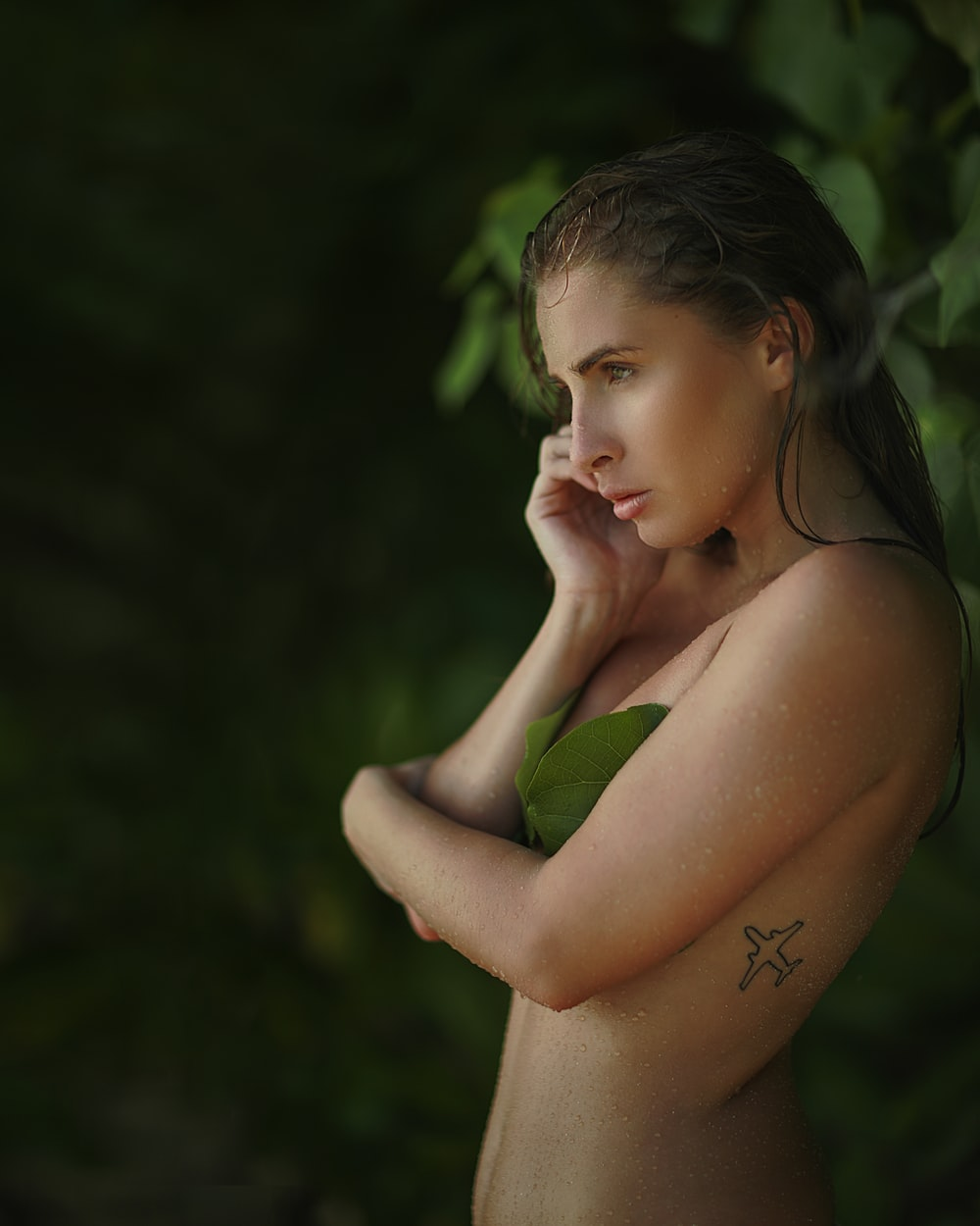 nude woman covering her chest with green leaf