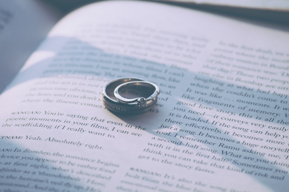 silver-colored ring on top of book page