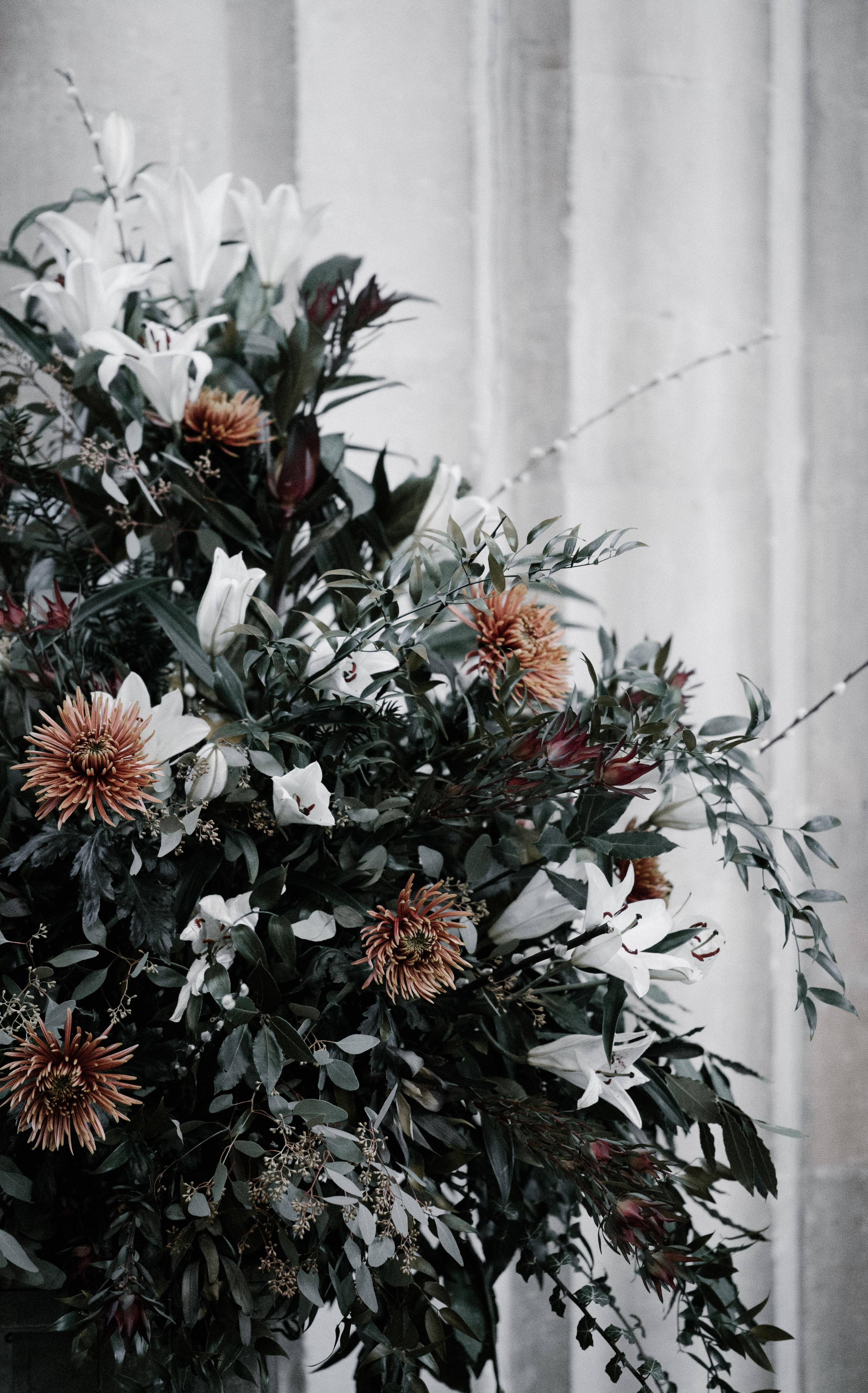 green, white, and brown flower arrangement decoration near white wall