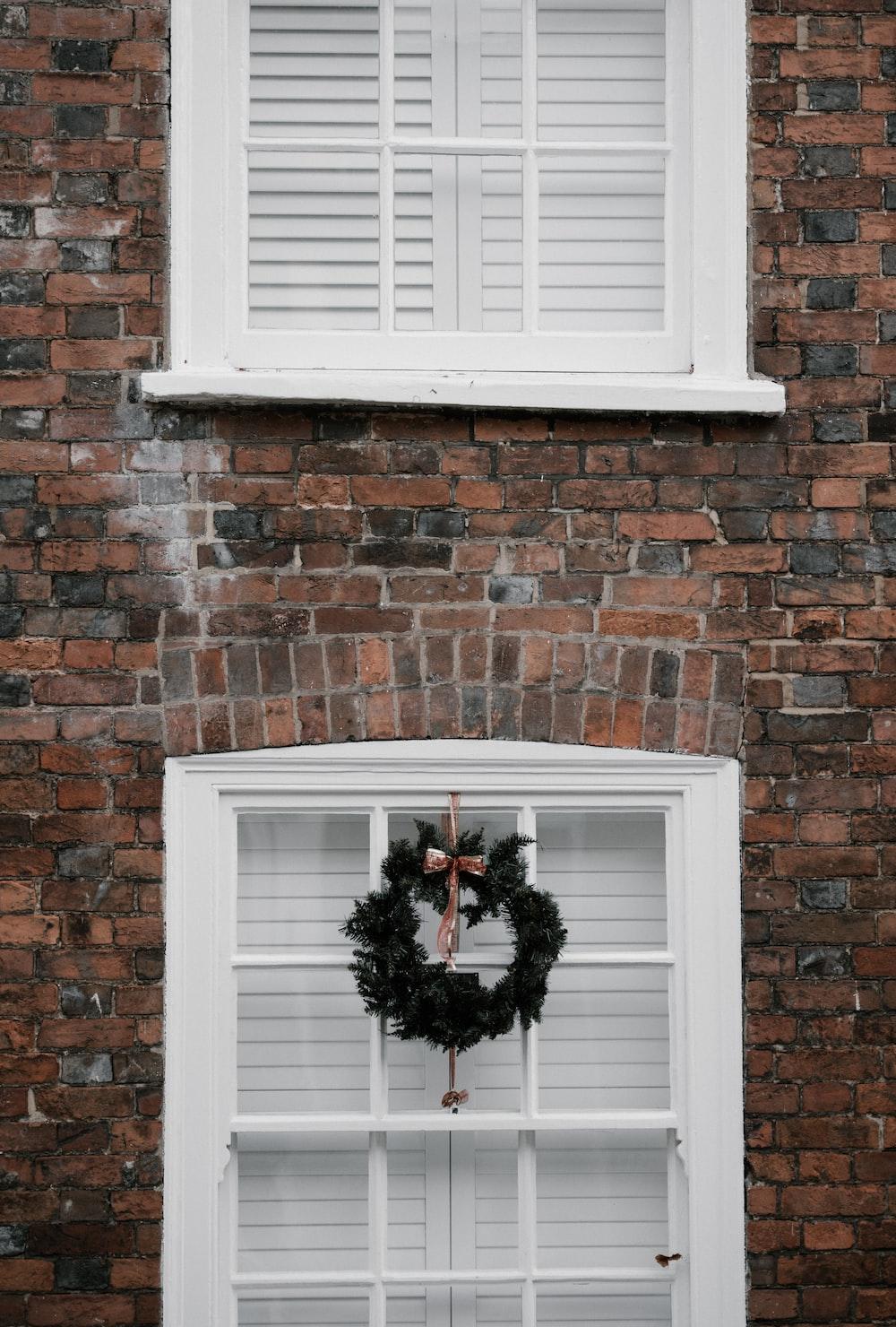 green wreath hanging on white window