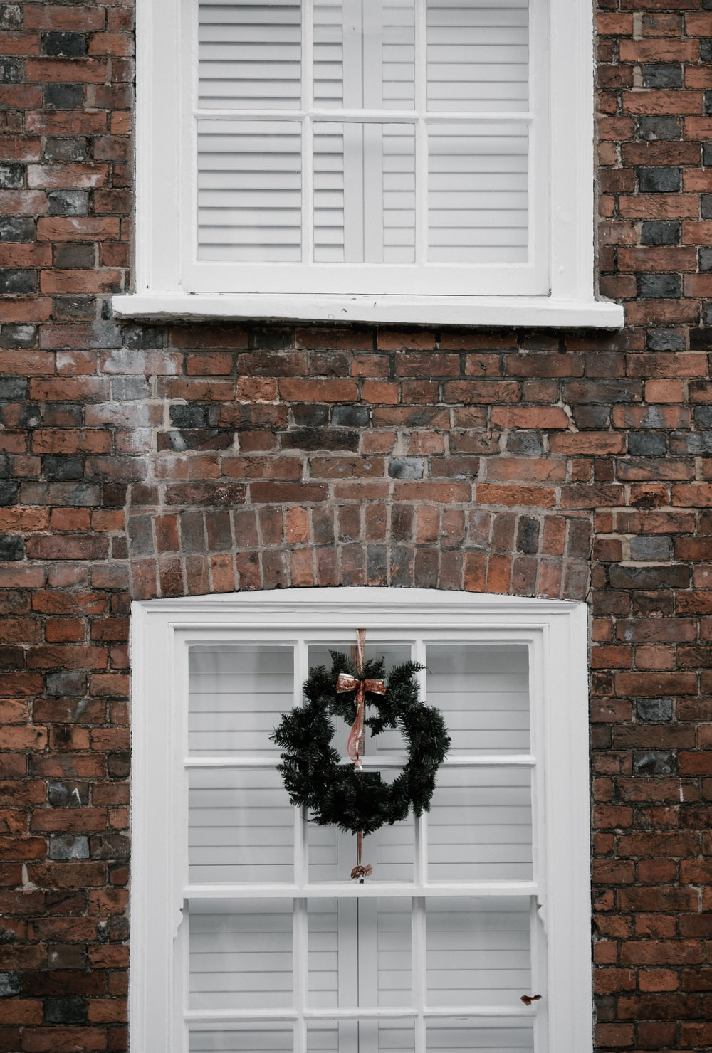 green wreath hanging on white window